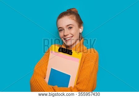 Cheerful Red Haired Caucasian Student With Freckles Is Holding Some Books And Posing On A Blue Backg