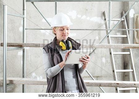 Woman Worker Builder Work With Digital Tablet, Wearing Helmet And Hearing Protection Headphones , On