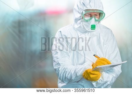 Female Epidemiologist In Protective Clothing Writing Research Report In Virus Quarantine, Medical Pr