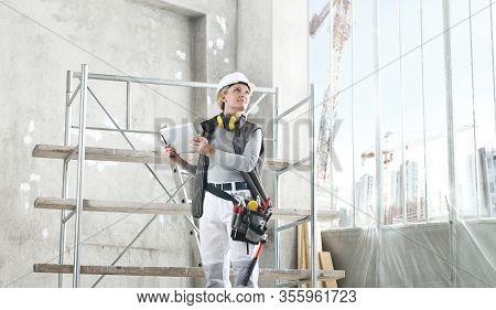 Woman Worker Builder Work With Digital Tablet, Wearing Helmet, Hearing Protection Headphones And Bag