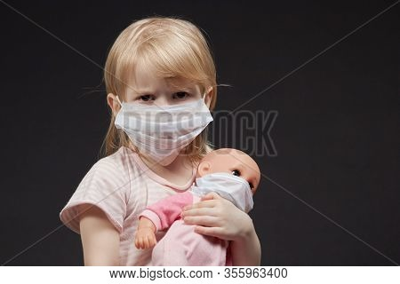Baby Girl In Medical Mask With A Doll In Her Hands