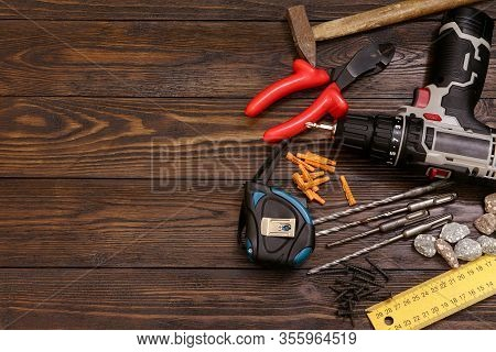 Carpenter Tools On A Wooden Table. A Screwdriver, Hummer, Drive Screws, Measuring Tape And Dowels On