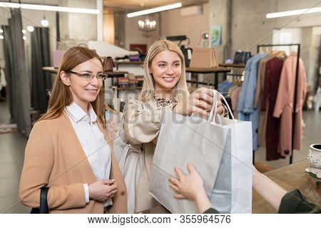 Happy young woman passing paperbags with purchases to shop assistant over counter while buying clothes in boutique