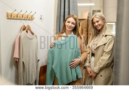 Two elegant pretty women standing in changing room in front of mirror while one of them choosing new sweater in the mall