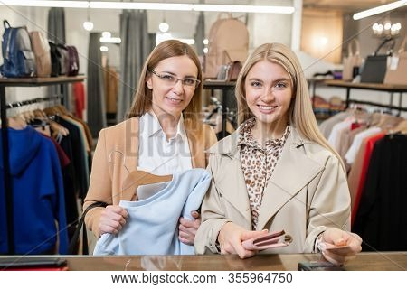 Two stylish women standing by counter and looking at you while one of them going to pay by credit card for new sweatshirt
