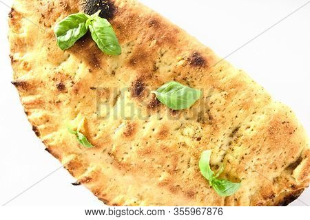 Traditional Italian whole calzone pizza with ham, cheese and tomatoes isolated on white background. Oven-baked folded kalzone stuffed with salami, vegetables, mozzarella, ricotta and parmesan cutout
