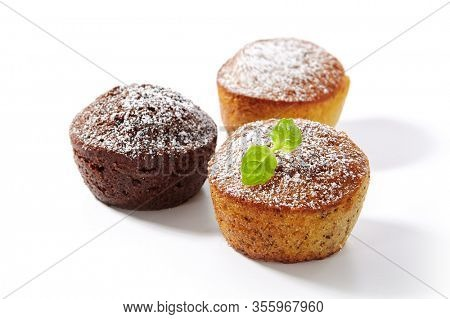 Chocolate cupcake, vanilla muffin and orange cake isolated on white background. Set of three delicious cupcakes decorated with powdered sugar and fresh mint leaves closeup
