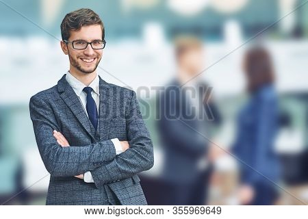 Confident And Successful Businessman. Cheerful Young Caucasian Man In Formalwear Keeping Arms Crosse
