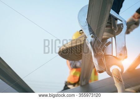 Construction Worker Wearing Safety Harness Belt During Working At High Place And Installing Concrete