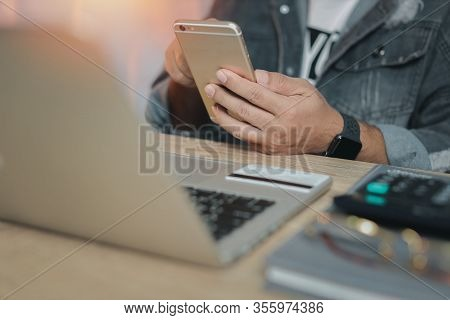 Man Hands In Grey Jean Sitting And Using Mobile Phone And Laptop Computer On Table With Credit Card