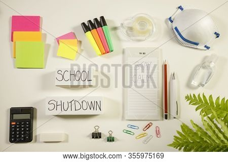Caronavirus School Shutdown Concept With Personal Mask, Hand Sanitizer And Stationery On White Flat
