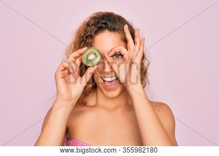 Beautiful woman with blue eyes wearing towel shower after bath holding kiwi fruit over eye with happy face smiling doing ok sign with hand on eye looking through fingers