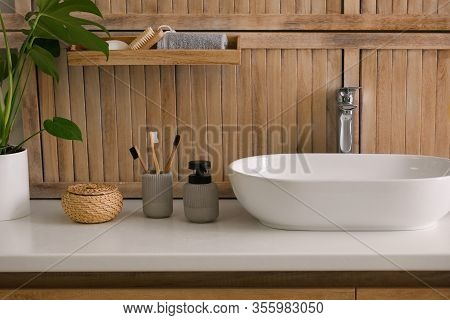 Toiletries And Stylish Vessel Sink Near Wooden Wall In Modern Bathroom