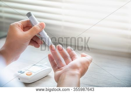 Closeup Woman Hands Using Lancet On Finger To Check Blood Sugar Level By Glucose Meter, Healthcare M