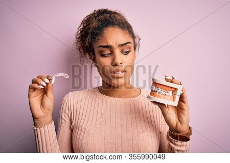 Young african american woman thinking and doubting holding professional orthodontic denture with metal braces and removable invisible aligner. Comparation of two dental straighten treatments