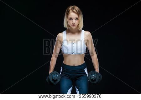 Close-up Portrait Of A Fitness Muscular Young Girl Posing With Dumbbells At The Gym Isolated On A Bl