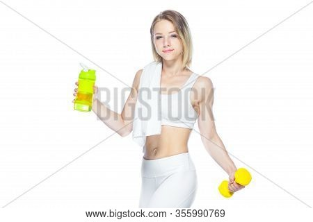 Beautiful Young Sportswoman Holding A Bottle Of Water, A Towel And A Dumbbell Over White Background