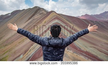 Asian Tourist Raising Hands Up At Vinicunca Rainbow Mountain Or Montana De Siete Colores, Located On