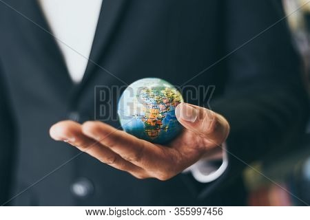 Business Man Holding Earth Globe Model In Hand And / Business Global And Travel Around The World Or