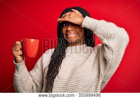 Young african american girl drinking a coffee cup over red isolated background stressed with hand on head, shocked with shame and surprise face, angry and frustrated. Fear and upset for mistake.