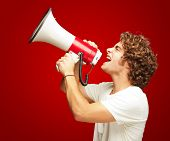 Portrait Of Young Man Shouting With A Megaphone Isolated On Red Background poster