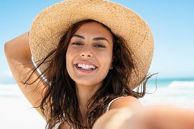 Portrait of beautiful young woman in casual wearing straw hat at seaside. Cheerful young woman smiling at beach during summer vacation. Happy girl with black hair and freckles enjoying the sun.