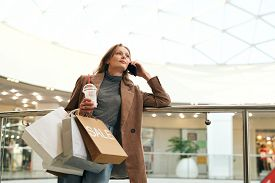Attractive young woman in stylish jacket leaning on railing and talking by phone in shopping mall