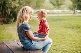 Young Caucasian Mother And Boy Toddler Son Sitting Together Face To Face. Family Mom And Child Talki
