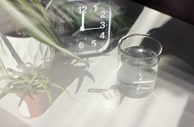 Fish Collagen Concept. Collagen Peptides Powder And Water. Through Window Look. Alarm Clock Near Spo
