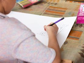 Cropped View Of Cute Kid Drawing On Paper With Pencils. Boy Drawing A Man. Children Art Lesson Conce
