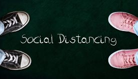 Two People Standing On Chalkboard With The Word Social Distancing In Between. Concept Of Staying Phy