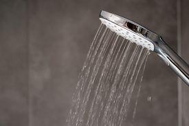 Water Flowing From Shower, Close Up. Modern Bathroom Interior. Chrome Shower Head With Splashing Wat