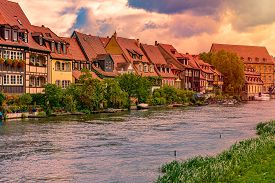 Bamberg City In Germany. River In Foreground. Sunset Cloudy Sky And Old Houses In Background