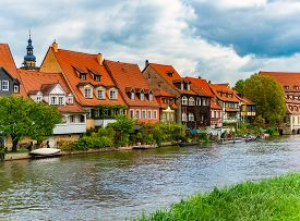 Bamberg City In Germany. River In Foreground. Blue Cloudy Sky And Old Houses In Background