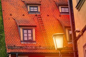 Old House Roof With Lies In Germany, Europe. Sunset Scene With Lantern Light. Architecture And Trave