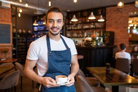Young cheerful waiter in white t-shirt and blue apron holding cup of cappuccino on saucer while looking at you