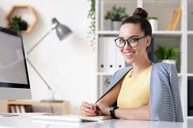 Happy young businesswoman in smart casual looking at you while sitting by desk in front of camera and planning work in office