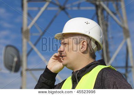 Ingeniero hablando por el teléfono celular cerca de torre de gsm