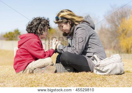 Single Mother And Son Praying Outdoors