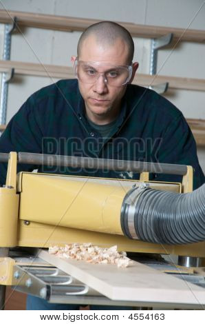 Wood Worker Using Power Tools In A Work Shop