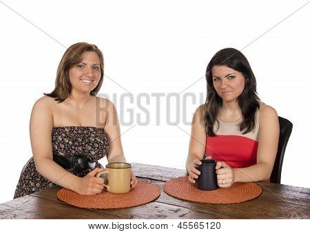 Two Women Sitting Having Coffee At Table