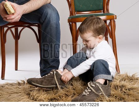 Child is putting on a big father's shoe. poster