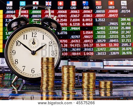 A Downtrend Columns Of Golden Coins With An Alarm Clock. Financial Chart As Background. Selective Fo