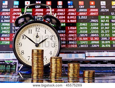 A Downtrend Stacks Of Golden Coins With An Alarm Clock. Financial Chart As Background. Selective Foc