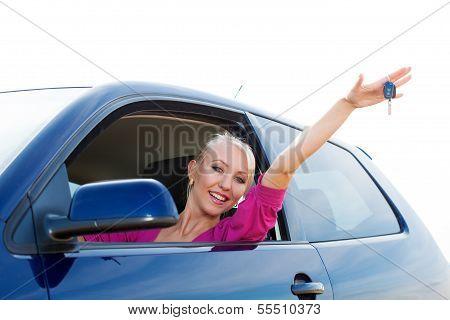Happy car driver woman showing new car keys in car window