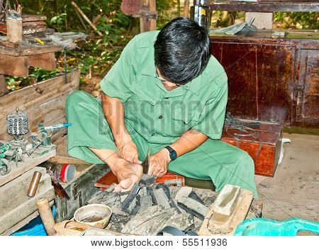 CU CHI, VIETNAM - NOVEMBER 17, 2013: Unidentified man makes shoes from old truck tires on November 17,2013 in Cu Chi, Vietnam.Cu Chi tunnels were the Viet Cong's base of operations for Tet Offensive.