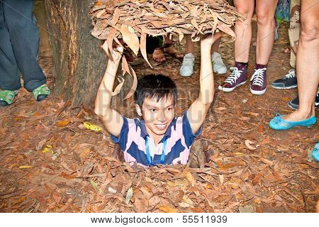 CU CHI, VIETNAM - NOV 17: Guide demonstrating how a Vietcong hide into the Tunnel on Nov 17 2013. Cu Chi, Vietnam.Cu Chi tunnels were the Viet Cong's base of operations for the Tet Offensive in 1968.