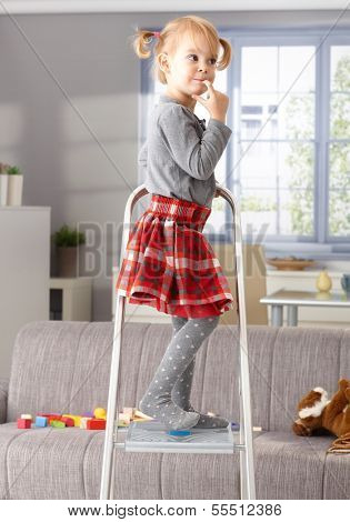 Elfish little girl standing on top of ladder, thinking impishly. poster