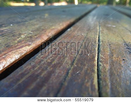 Wooden table bench shot in perpective on a sunny day, poster