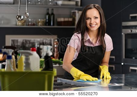 Beautiful cheerful brunette woman in gloves cleaning modern kitchen